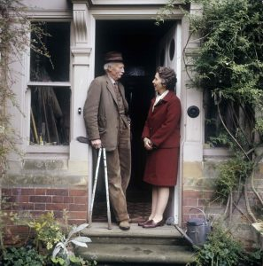 Colour photograph of Valerie Finnis and husband Sir David Scott on the steps at Dower House, Boughton, Northamptonshire. ©Valerie Finnis/RHS Library Collections